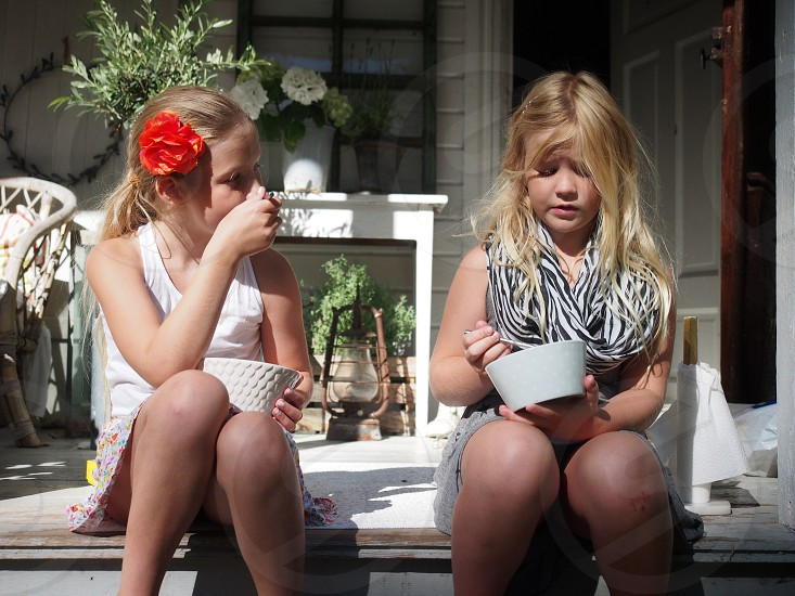 Two sisters sitting in the porch discussing and eating ice cream. Long hair flower in hair sunny two persons children Sweden summer  photo