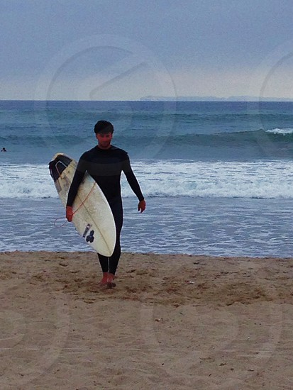 man holding white surfboard photo