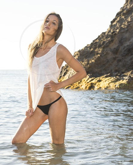 woman in white tank top and black bikini bottom standing on body of water beside brown rock during daytime photo