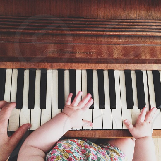 baby and adult hands on brown wooden piano photo