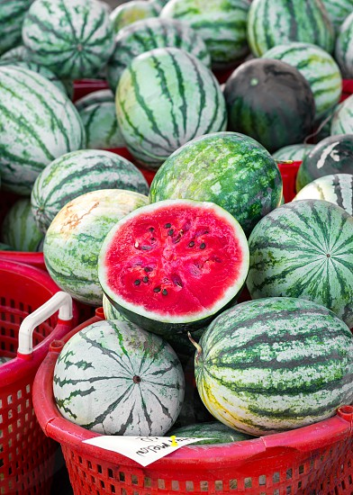 Fresh watermelons with a cut half for sale at a local farmer's market photo