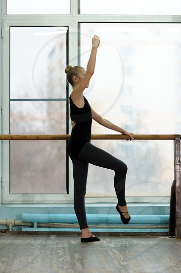 Young female ballet dancer exercising at the barre by the window in studio. Ballet classes photo