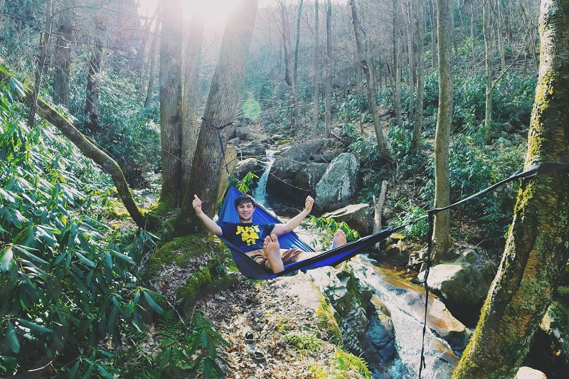 man in black nike crew neck t-shirt lying on blue hammock at the forest at daytime photo