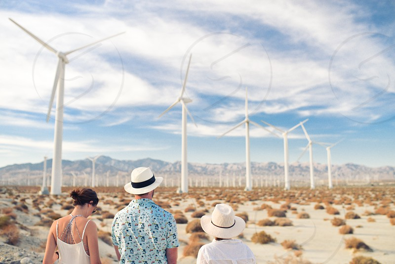 person wearing white black panama hat and blue t shirt between woman wearing white spaghetti strap top and person wearing white hat and white shirt looking at the lines of white wind turbines in the field of brown bushes under blue sky white cirrus clouds photo