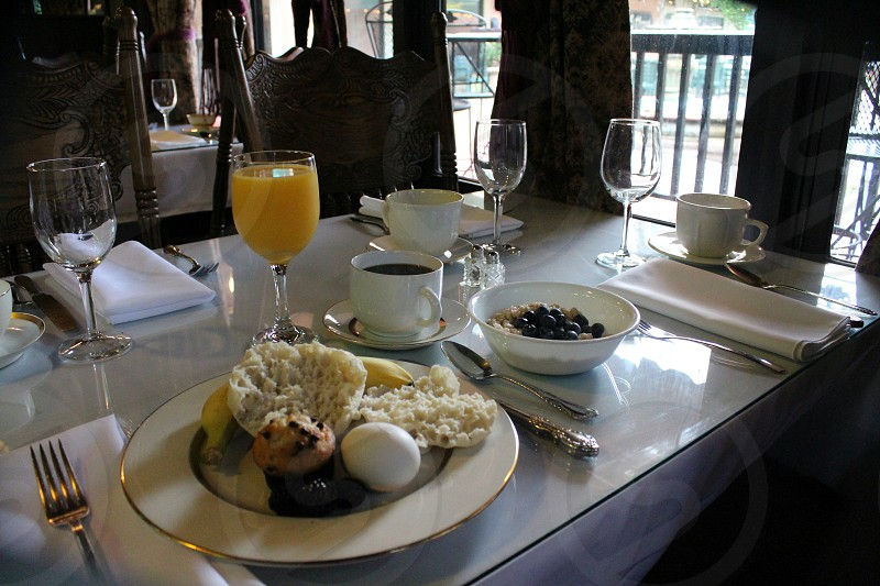 Healthy breakfast of English muffin banana oatmeal with fruit hard boiled egg orange juice and coffee in formal dining room. photo