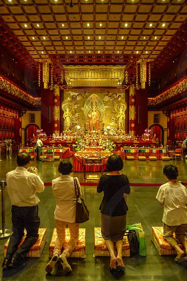 Praying people in Buddha tooth temple in Singapore photo