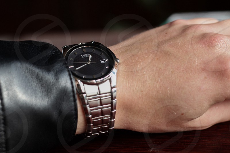 hand with silver analog watch black face citizen photo