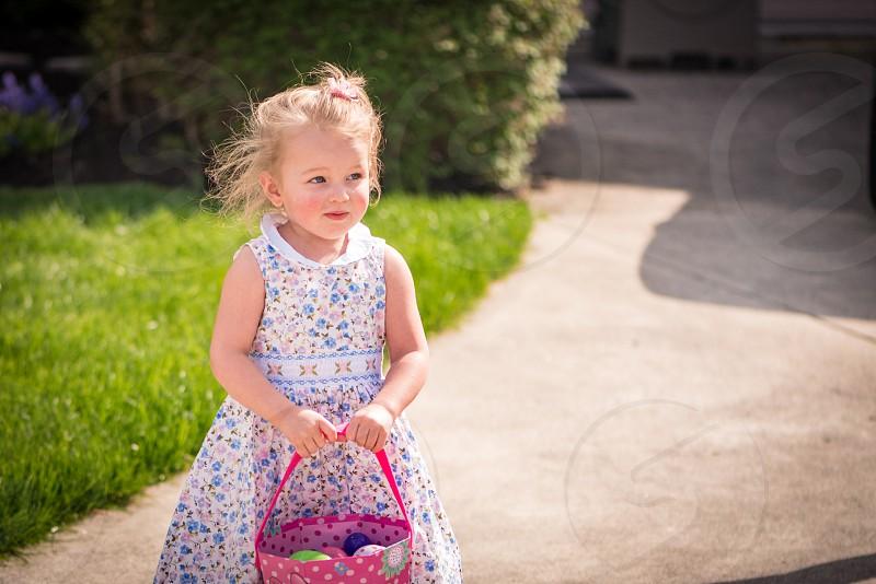 Little girl hunting Easter eggs in a white dress. photo