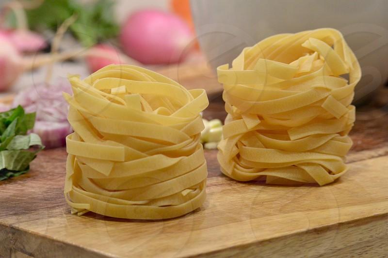 flat spaghetti clumps on brown board photo