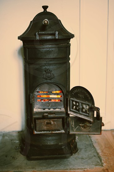 In front of the fire place a vintage fire burner warming up the room photo