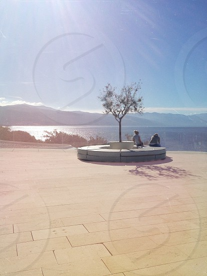 woman seated on round concrete chair looking at sea photo