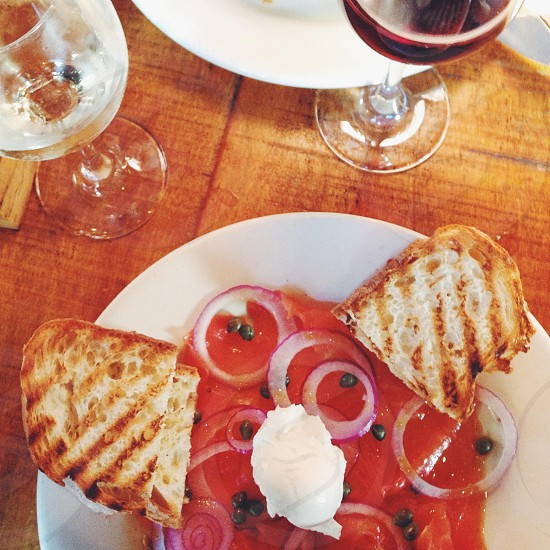 Grilled ciabatta bread smoked salmon cream cheese onions & capers for brunch. Plus a glass of wine. photo
