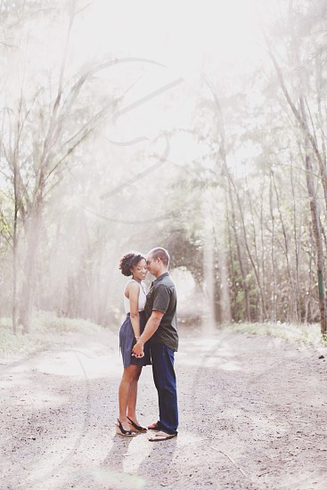 couple standing in tree lined path at winter photo