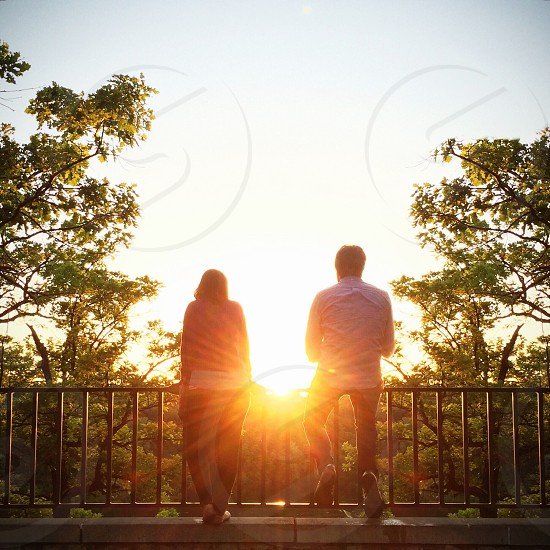 man and woman leaning on metal railings photo