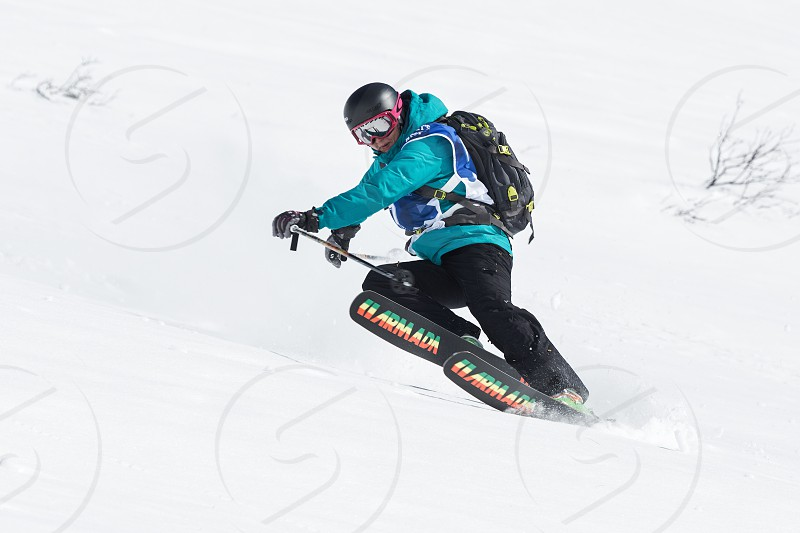 "KAMCHATKA RUSSIA - MARCH 9 2014: Girl skier rides steep mountains. Competitions freeride snowboarders and skiers ""Kamchatka Freeride Open Cup"". Russia Far East Kamchatka Peninsula. photo"