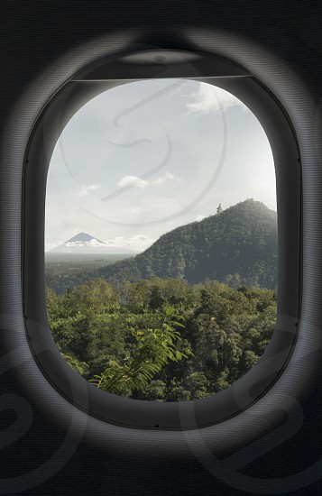 Mountain green tropical forest and sky view from an airplane window. Go Travel booking concept photo