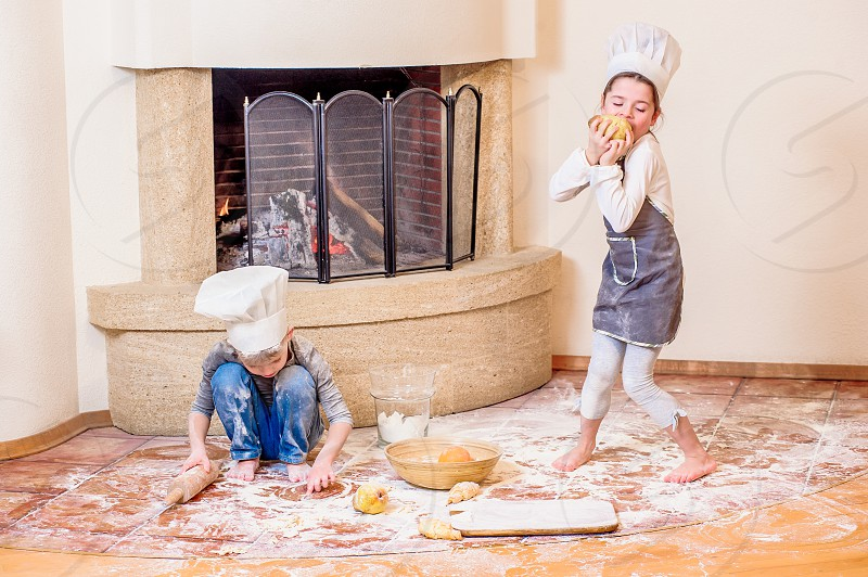 Boy and girl in chef's hats near the fireplace sitting on the kitchen floor soiled with flour playing with food making mess and having fun photo