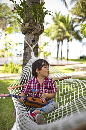 mixed Eurasian boy playing guitar and singing while relaxing on a hammock photo