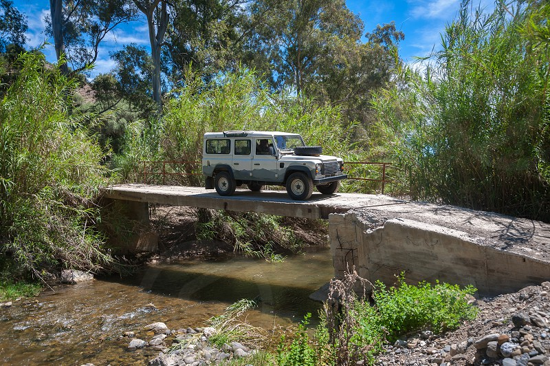 Rural Andalucia. Spain. Europe. Driving across river in 4x4 on derelict unsecured concrete bridge. photo