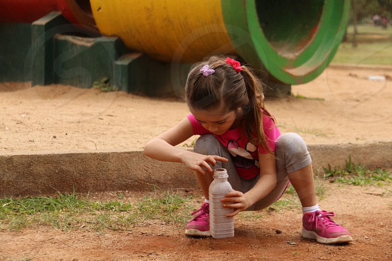 girl in pink shirt putting sand on a plastic bottle photo