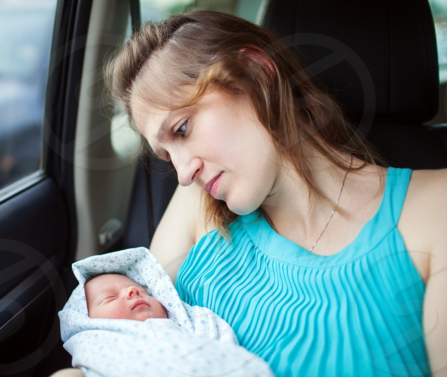 Young mother holding newborn wrapped in baby blanket while sitting in the car. Woman looking at her baby with deep feelings expressed in the eyes photo