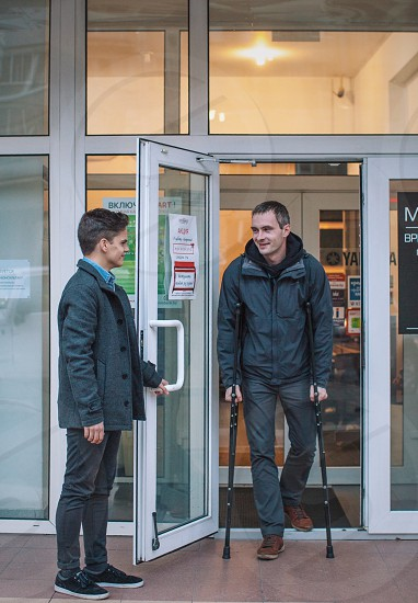 man with black hair opening door for man using crutches photo