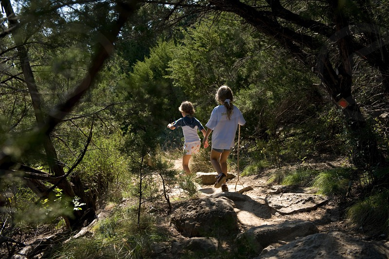two girls running down a path in the woods photo