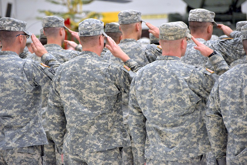 arm forces in camo suit doing salute photo