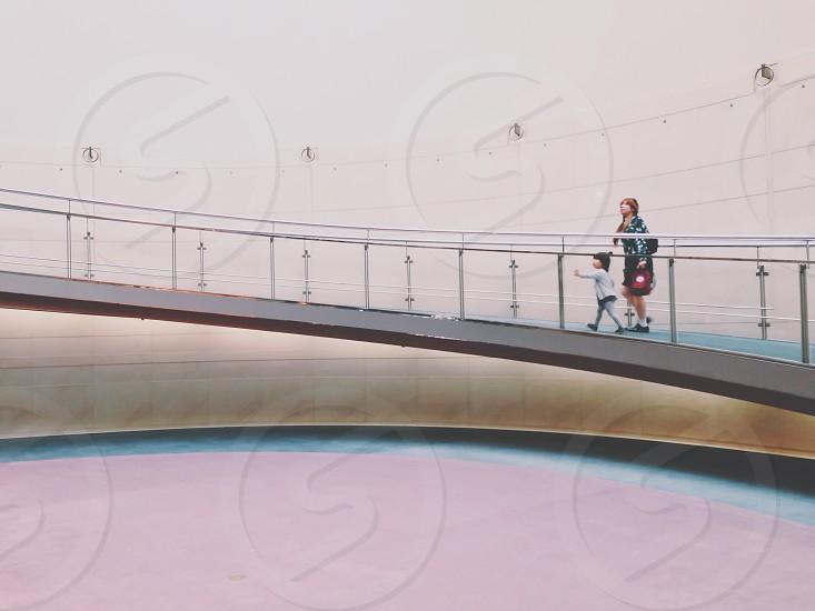 woman and child walking on bridge photo