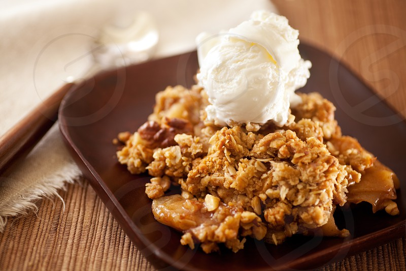 Hot dessert with vanilla ice cream. Apple Crisp made with oatmeal sugar walnuts and appples. Nice treat on cold winter days. photo