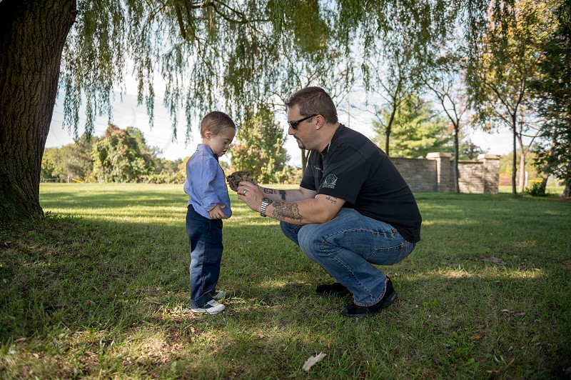 Dad teaching his Son (with special needs - Down syndrome) about nature at the park photo