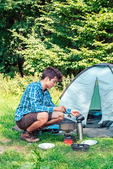Spending a vacation on camping. Young man preparing a meal outdoor next to tent photo