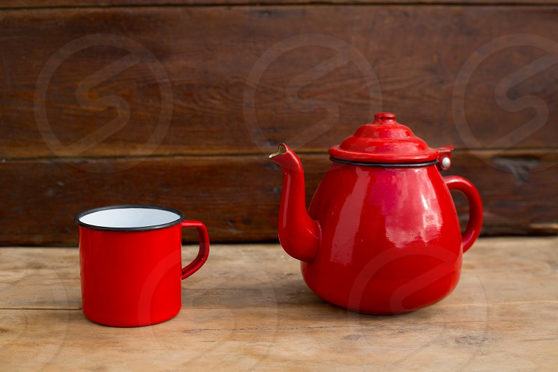 retro old vintage teapot and red cup in wooden background photo