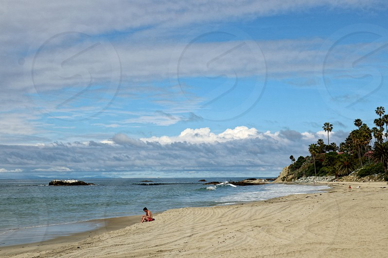 Seen in the distance a many reads a boos alone on a sandy beach near the ocean photo
