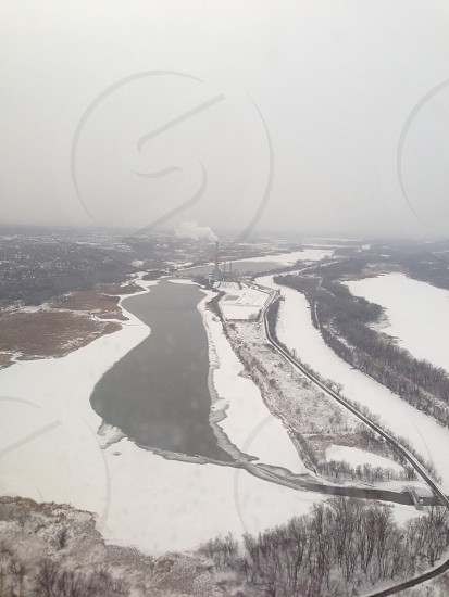 aerial view of body of water surrounded by snow covered ground during daytime photo