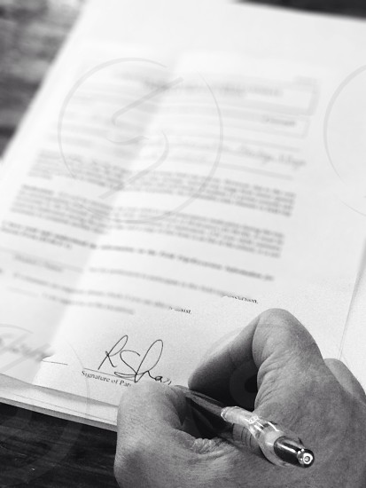 black and white photo of someone signing a contract photo