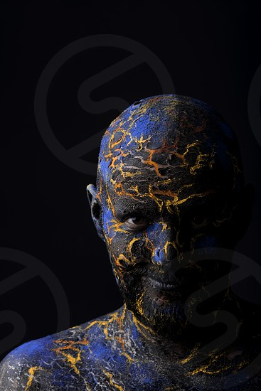 Conceptual Portrait of a brutal man painted in face art style over black background photo