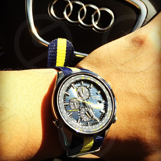 person wearing round black Citizen chronograph watch with yellow and blue striped strap photo