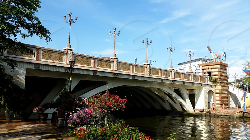 white and brown concrete bridge above a river with flowers during daytime photo