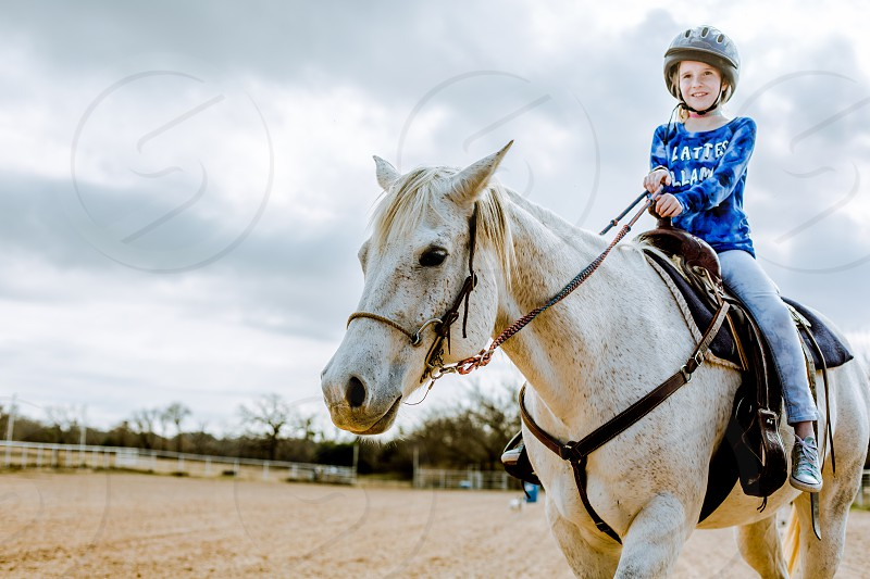 A young girl riding a white horse on a ranch. photo