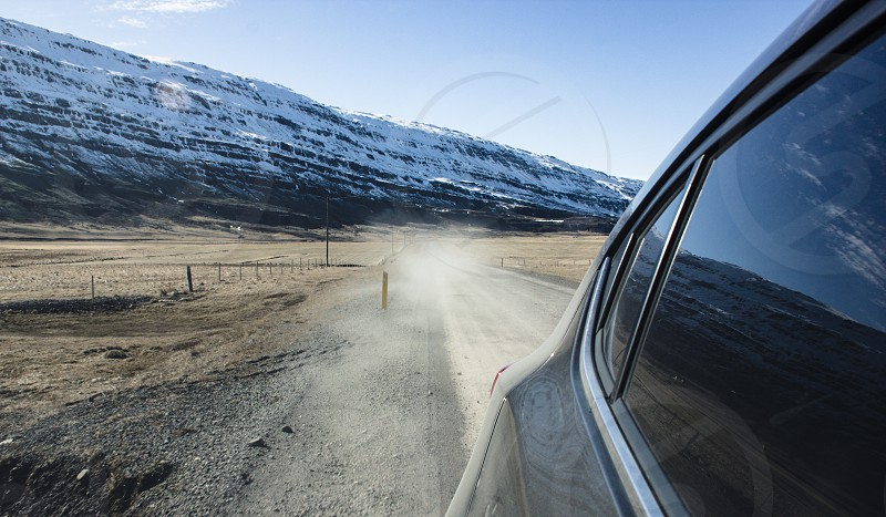 car window view of roadway beside snow mountain cliff hills during daytime photo