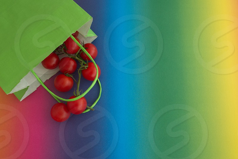 Directly above shot of the tomato and green paper bag on rainbow colored background photo