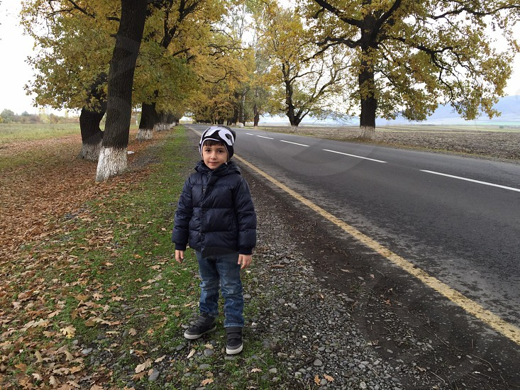 boy in bubble jacket standing on roadside during daytime photo