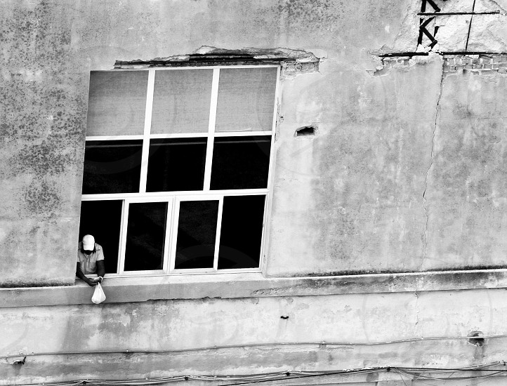 man looking out window old window old building man with white hat man with bag photo