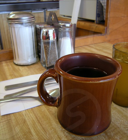 Brown coffee cup on table with silverware salt and pepper and condiments photo