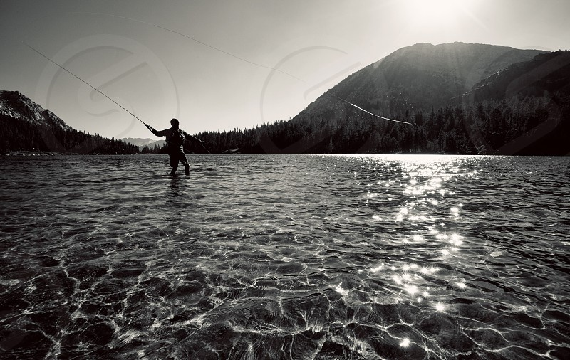 Fly fishing on a lake in the Sierra Nevada Mountains near Mammoth Lakes CA  photo