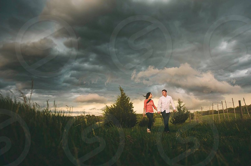 Engagement couple walking storm storm clouds clouds bad weather love country field green nature walk holding hands.  photo