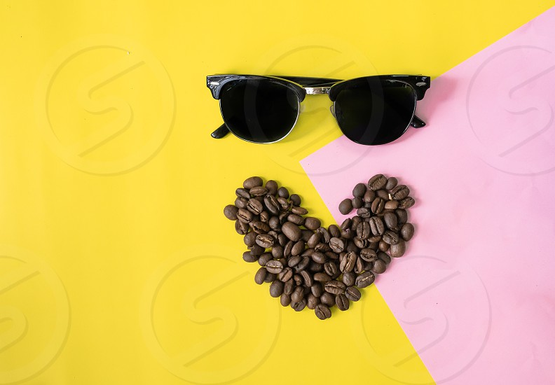top view flat layer funny face made from coffee beans in smile  icon shape  and sun glasses on two tone multicoloured  background photo