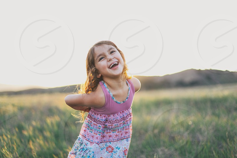 girl in multicolor floral tank dress with brown hair smiling in field daytime photo