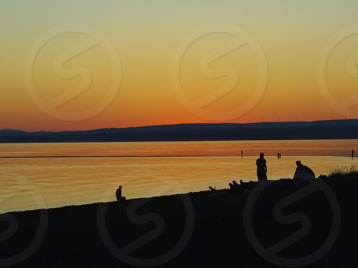 People enjoying sunset at the beach photo